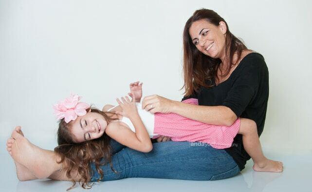 ילדה נשענת על רגלי אמה כשהאם מסתכלת על הילדה מסדרת צילומי משפחה וילדים בסטודיו אנדה יואל