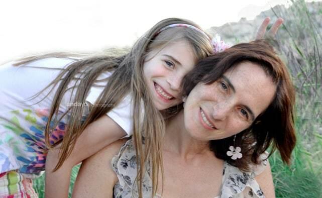 ילדה מחייכת ונשענת על אמה בצילומי משפחה בטבע בירושלים