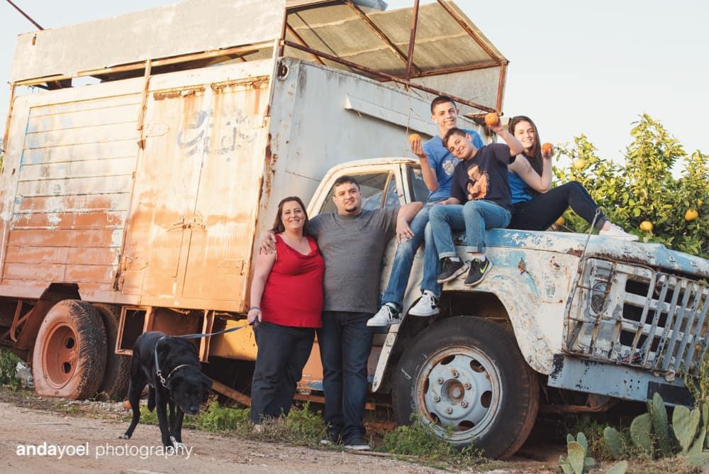 מיכל בן זוגה הילדים והכלב על רקע משאית ישנה בצילומי הריון ומשפחה בטבע