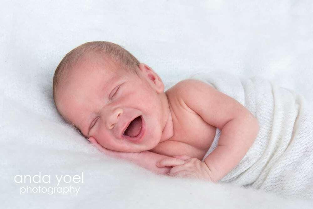 תינוק ניובורן מחייך על רקע שמיכה לבנה - מסדרת צילומי ניובורן בסטודיו אנדה יואל