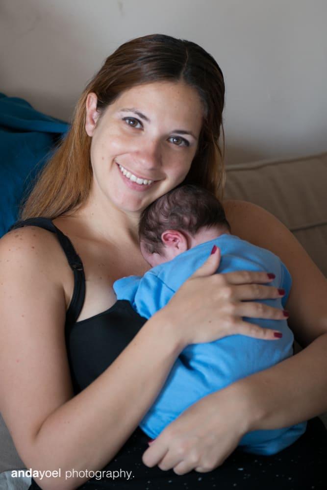 אמאמחבקת תינוקה הניובורן ומחייכת למצלמה בסדנת הצילום של אנדה יואל