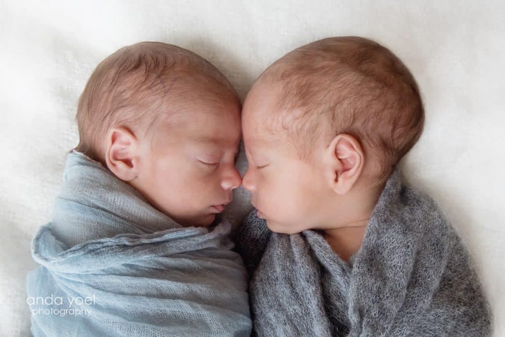 תאומים בנים עטופים בבד בצבע תכלת מביטים זה בזה מתוך סשן צילומי ניובורן תאומים בסטודיו