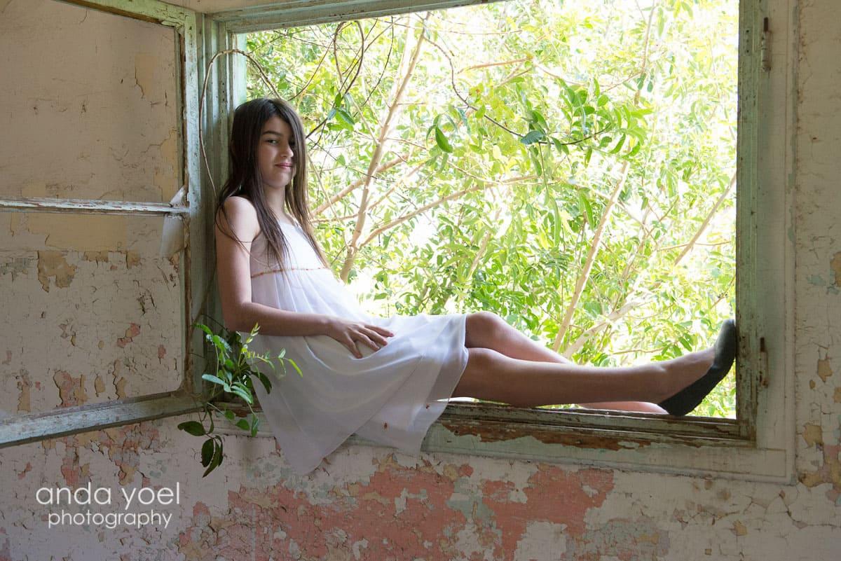 ילדת בת מצווה יושבת בתוך חלון עץ - מתוך סדרת צילומי בוק בת מצווה בטבע - אנדה יואל