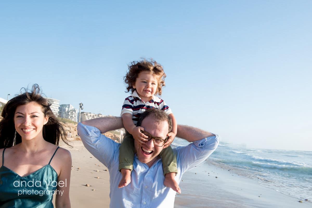 תינוק חייכן על הכתפיים של אבא על שפת הים יחד עם אמא, מצילומי משפחה בים של אנדה יואל
