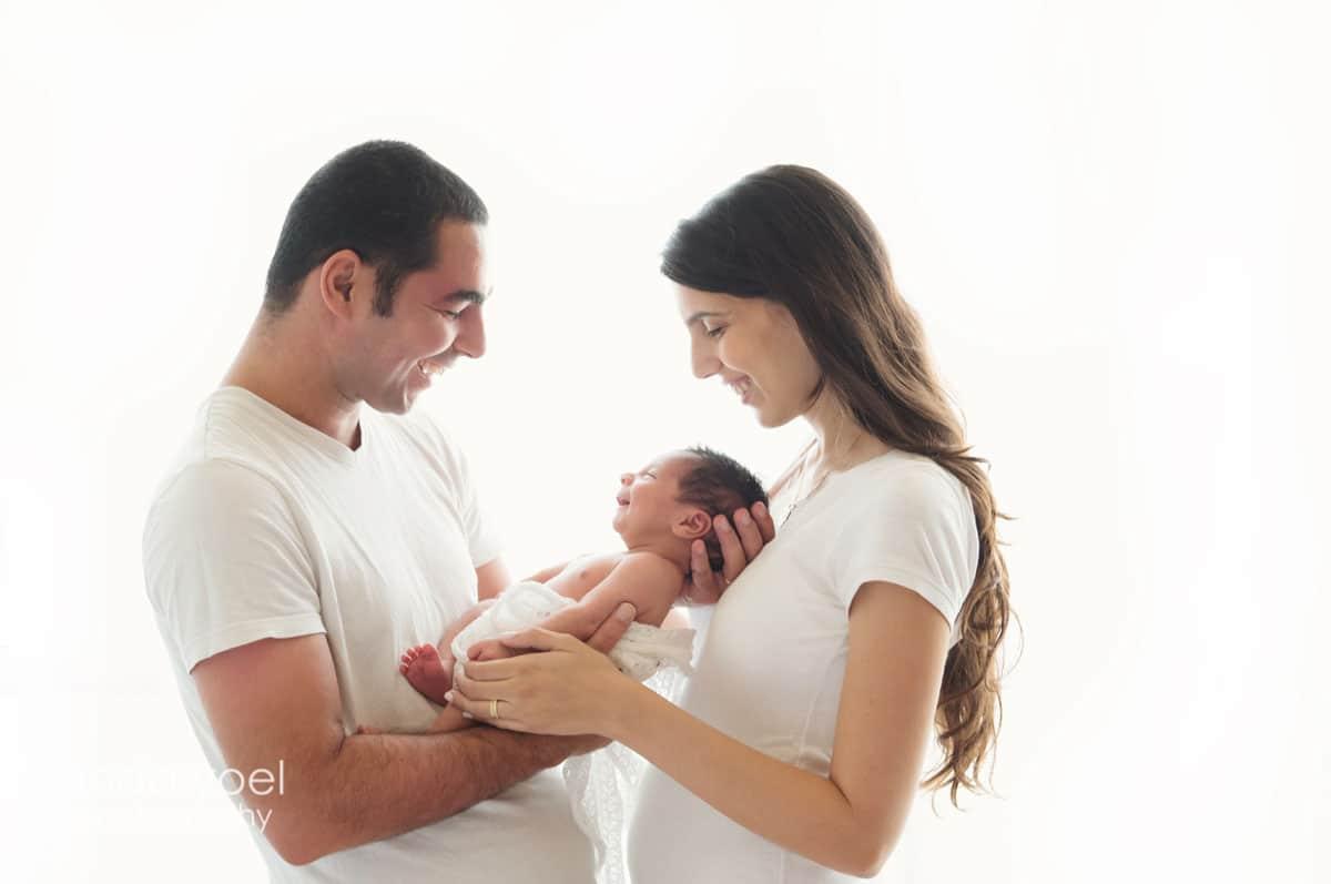 הורים לבושים לבן מחזיקים את תינוק אבא מחייך לתינוק והתינוק מחייך חזרה - מסדרת צילומי ניובורן אנדה יואל