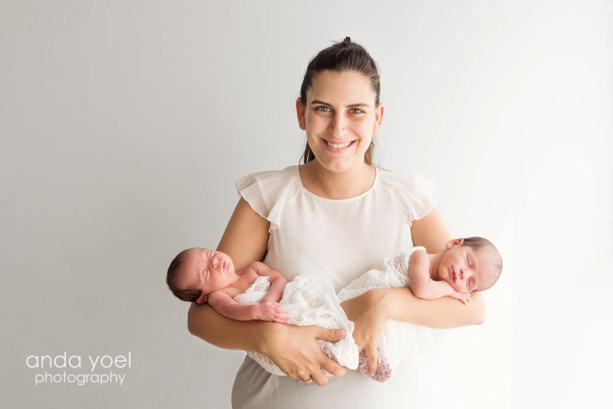 אמא חייכנית מחזיקה תאומים ניובורן תאומים בן ובת כל אחד ביד אחרת בתאורה טבעית - אנדה יואל