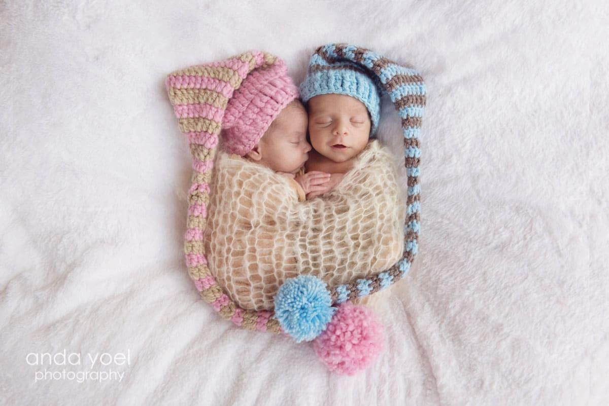 תינוקות ניו בורן בן ובת עם מצנפת תכלת ומצנפת ורודה - מסדרת צילומי ניובורן באור טבעי - אנדה יואל